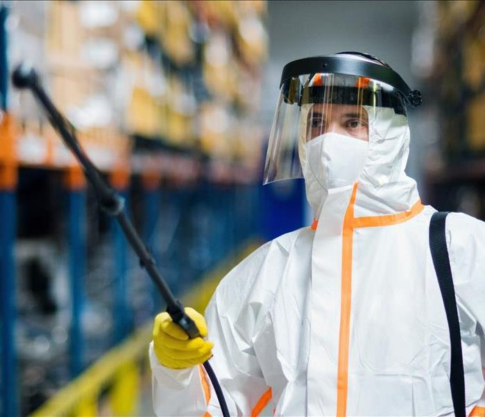 Male worker with protective mask and suit disinfecting industrial factory with spray gun